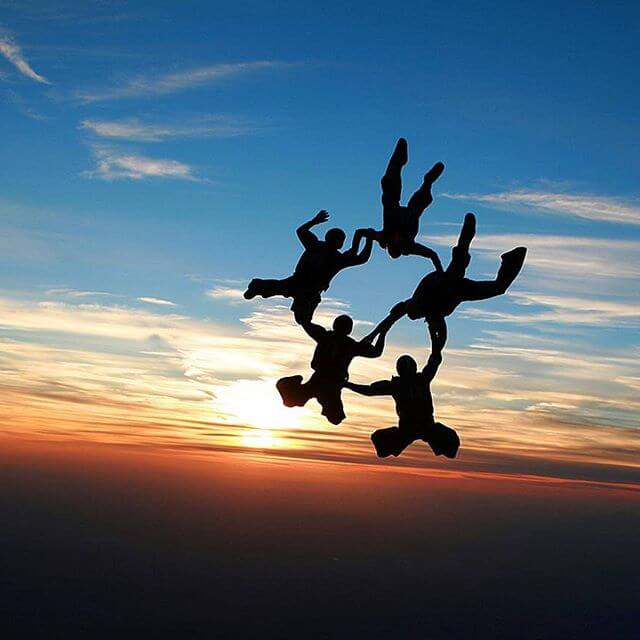 Wings of Blue members skydiving in formation with sunset in background