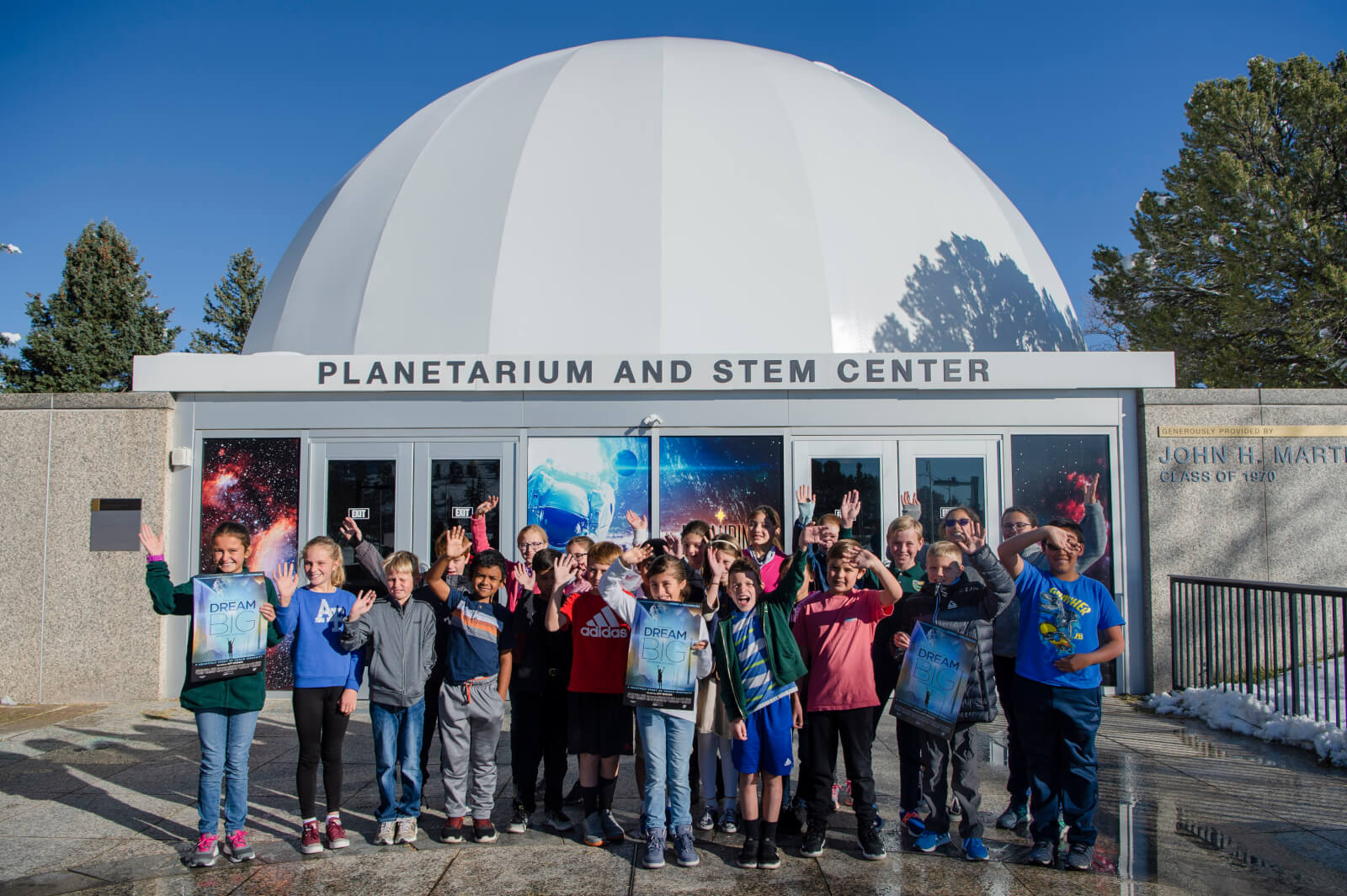 "Students from St. Paul Catholic School in Colorado Springs wave for the camera following the planetarium's ""Dream Big: Engineering our World"" show at the Air Force Academy, Colo., Oct. 25, 2019. The school's STEM teacher said the experience was incredible and inspiring and the new multimedia capabilities of the planetarium captivated him and the students. (U.S. Air Force photo by Trang Le)"