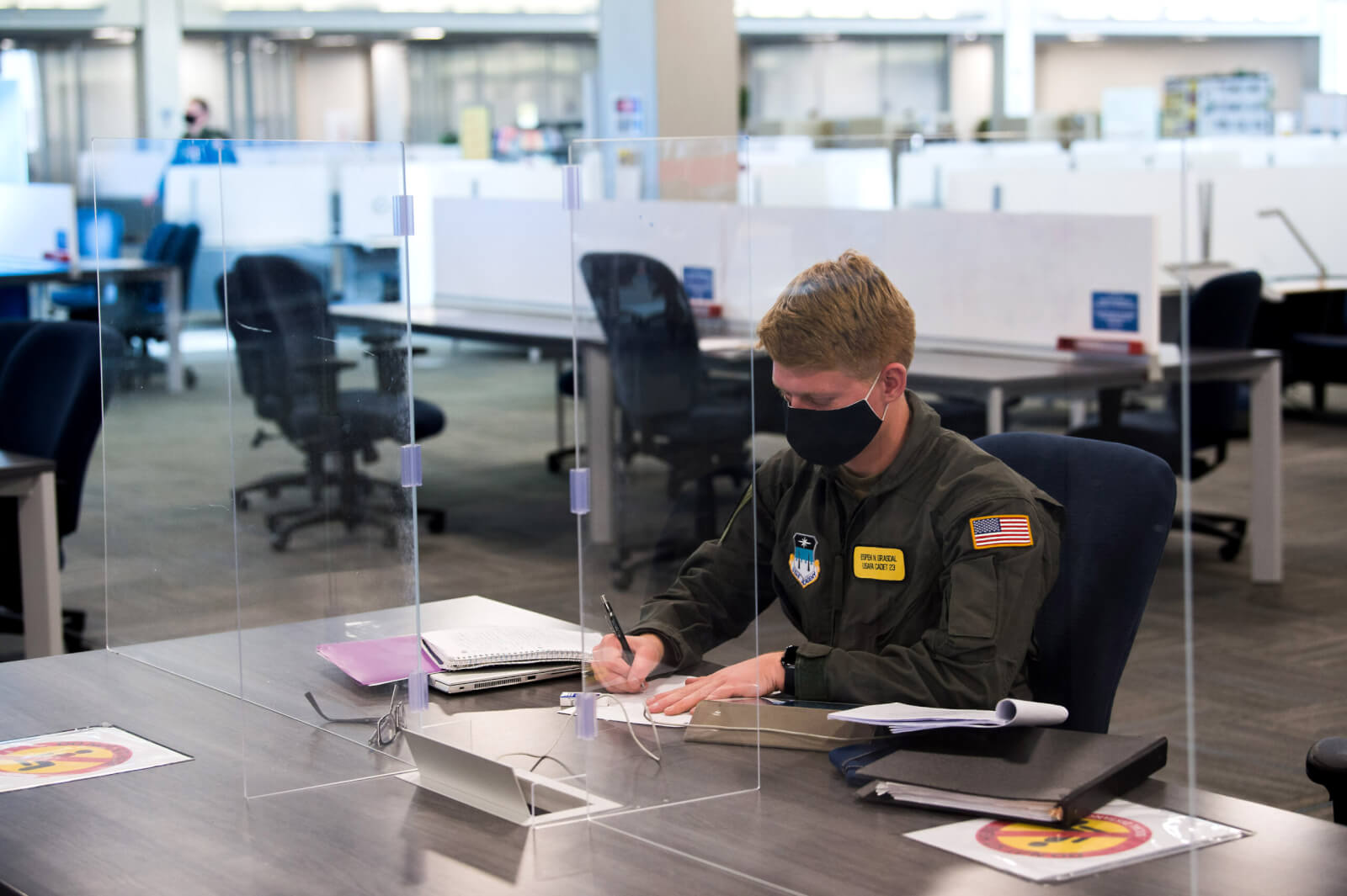 Cadet wearing mask working behind plexiglass