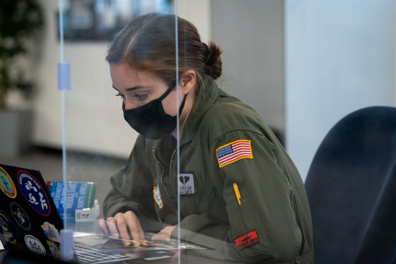 Cadet at laptop computer with Plexiglass shield