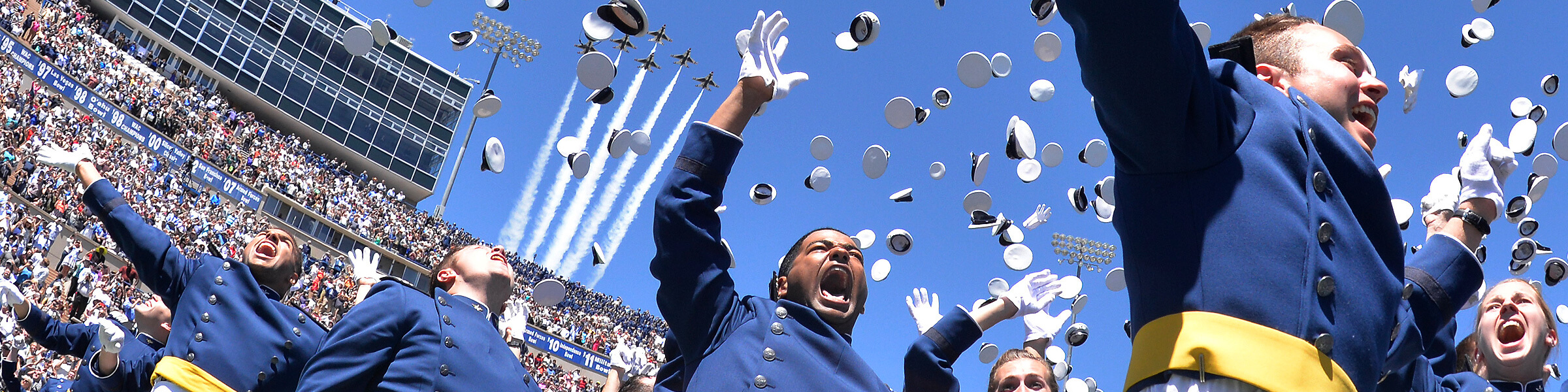 Banner image for graduation 2018 showing the cade hat toss as Thunderbirds fly over head.