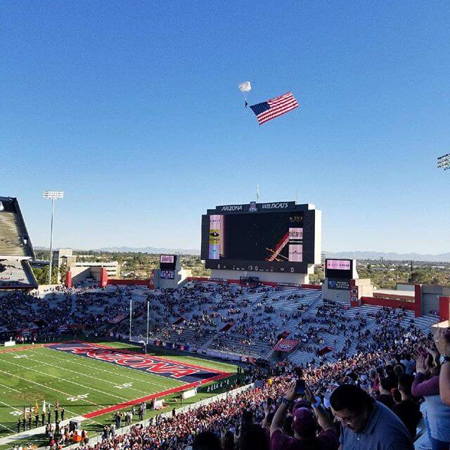 Wings of Blue skydiving with flag over stadium