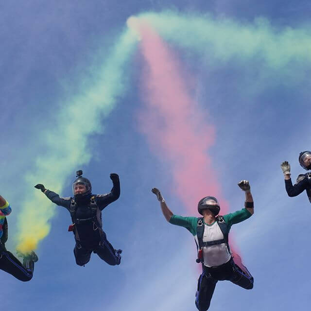 Wings of Blue members skydiving in formation with colored smoke