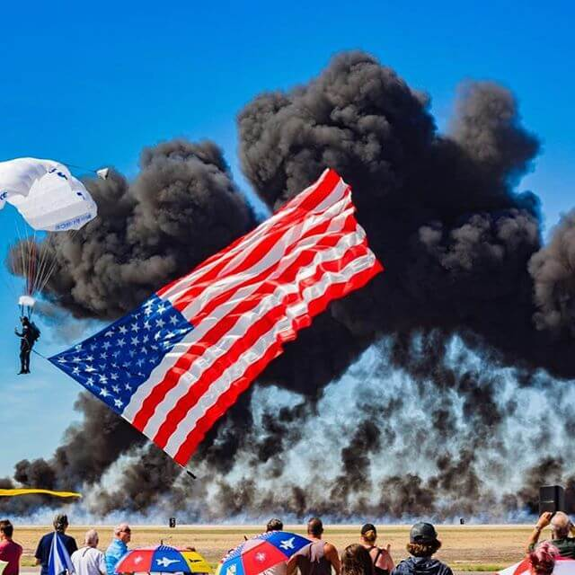 Wings of Blue skydiving with flag in front of smoke