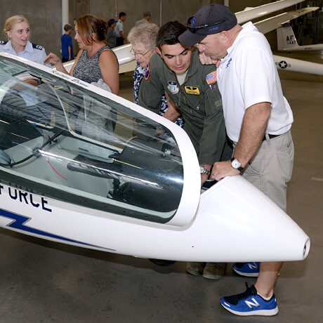 image of a cadet talking to a Parents' Weekend participant at the Aifield Open House.