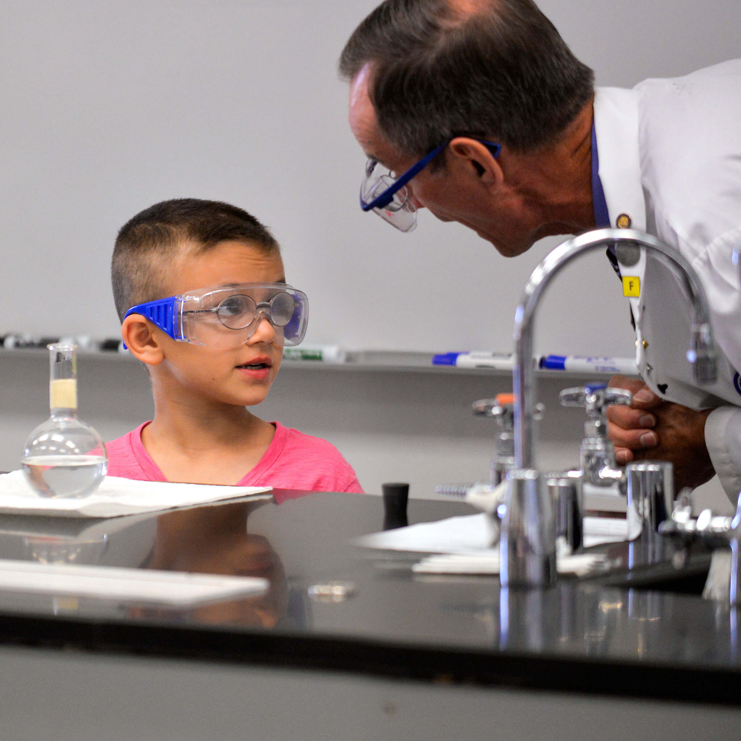 image of a chemistry instructor interacting with a young participant.
