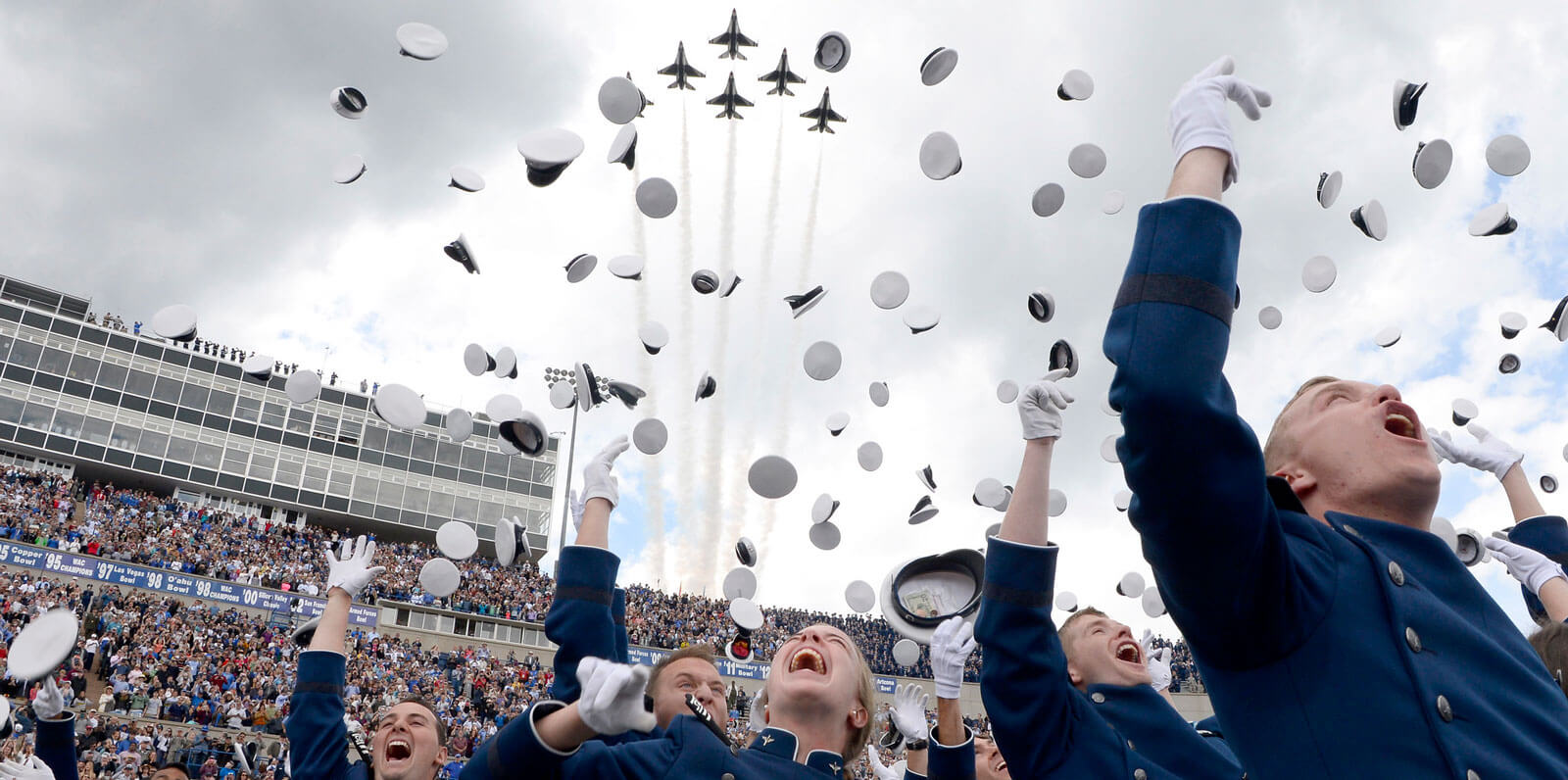 cadets throwing hats in air at graduation