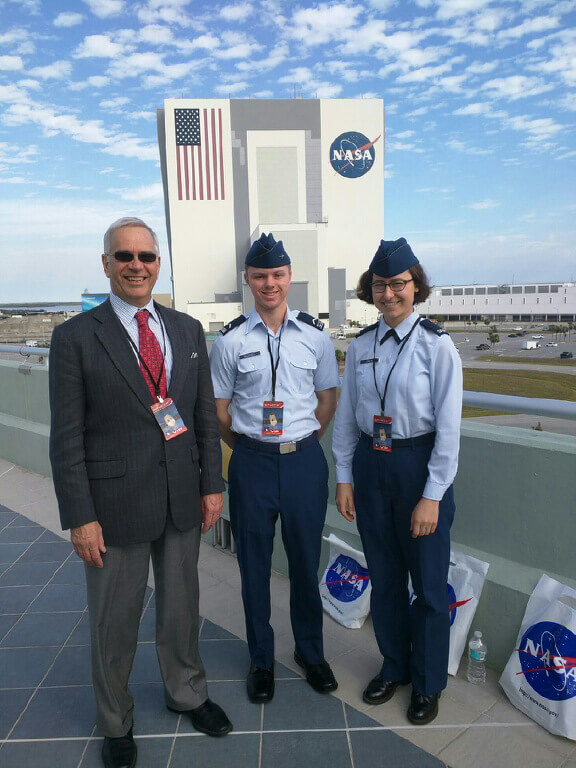 Dr. Geoff McHarg (left), director of the Space Physics and Atmospheric Research Center at the U.S. Air Force Academy, stands with Cadet 3rd Class Nick McDaniel (middle) and Cadet 4th Class Sequoia Chun, in front of the Vehicle Assembly Building at Cape Canaveral, Florida, Feb. 19, 2017. The trio attended the Space-X CRS-10 launch taking the latest Academy space experiment to the International Space station