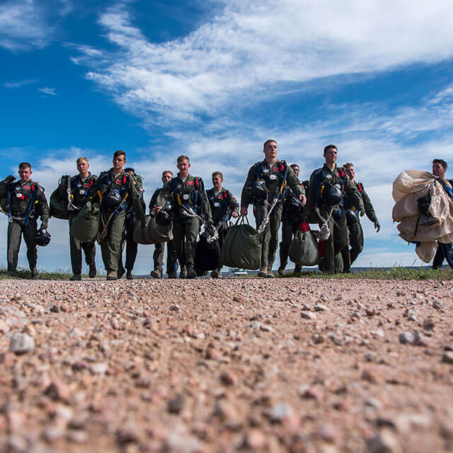 Skydiving cadets carrying gear