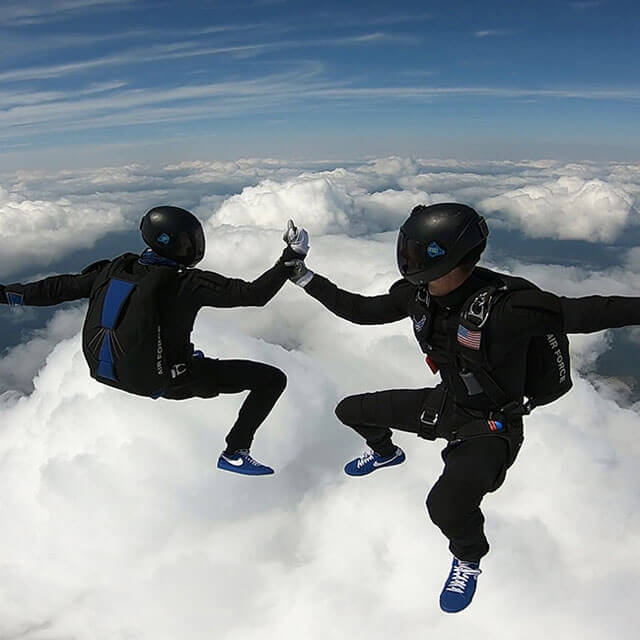 Two competition team members grasping hands in skydive