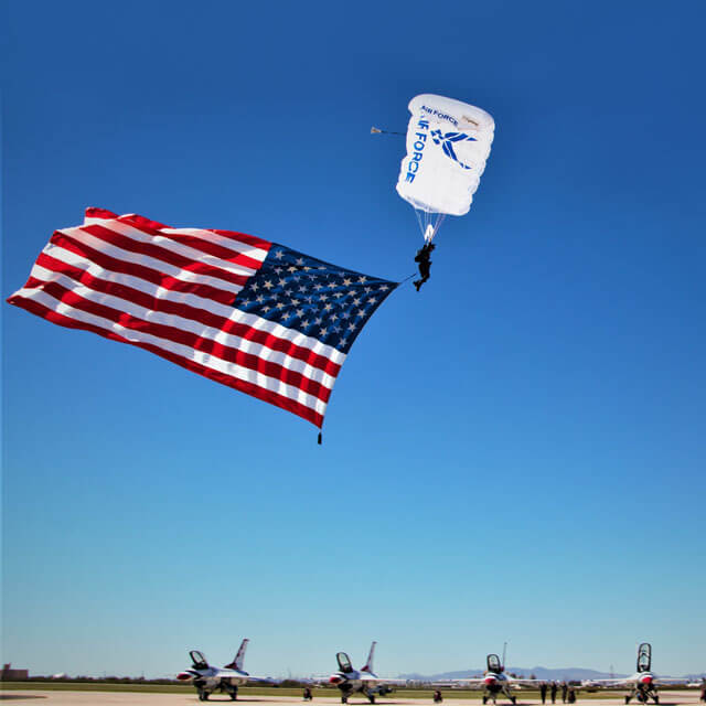 Wings of Blue member trailing US flag above Thunderbirds on airfield