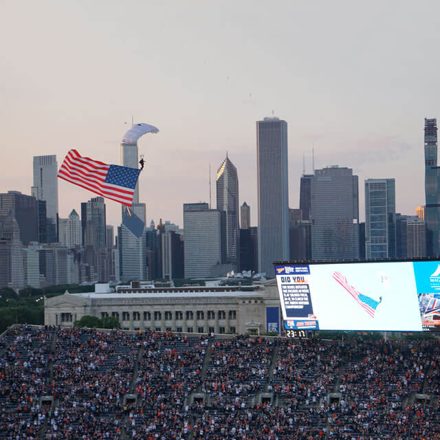 Wings of Blue member trailing flag descending into Soldier Field in Chicago