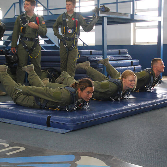 Cadets practicing skydiving form on mat